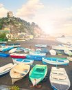 Boats on beach at sunset in small fishing village Royalty Free Stock Photo