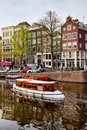 Boats on canal in amsterdam boat a and historic terraced houses the city of netherlands north holland province Royalty Free Stock Photos