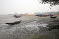 Boats of fishermen stranded in the mud at low tide on the river Malta near Canning Town, India Royalty Free Stock Photo