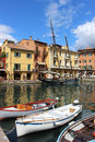 Boats in harbor at malcesine on lake garda italy view across the lago di with small rowing near the camera and a tall ship Royalty Free Stock Image