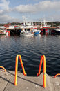 Boats moored in killybegs with steps fishing the calm waters of harbour ladder at foreground Stock Photography