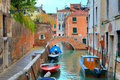 Boats on narrow canal among old colorful brick houses and small bridge on background in venice italy Royalty Free Stock Images
