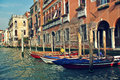Boats and old buildings on grand canal in venice italy tied next to typical brick building toned image Royalty Free Stock Image