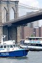 Boats pass under the Brooklyn Bridge Stock Images