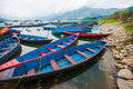 Boats on phewa lake pokhara nepal picture of resting the bank of in a mountain is visible in the background Stock Photo
