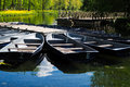 Boats on the pier in the city Park. Summer Park with a lake. Docked wooden rowing boat. Royalty Free Stock Photo