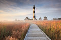 Bodie island lighthouse and boardwalk with fog early in the morning as the still lay in the fields the sun began to rise in north Stock Photography