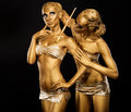 Body Art. Woman painting Body with Paint Brush in Golden Color. Gold Make Up Stock Photo
