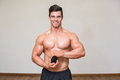 Body builder holding bottle with supplements in gym portrait of male Stock Images