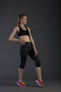 Body of slim female in activewear doing posin on gray low key perfect blonde sport woman Royalty Free Stock Photo