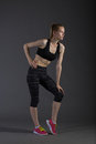 Body of slim female in activewear doing posin on gray low key perfect blonde sport woman Royalty Free Stock Photos