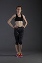 Body of slim female in activewear doing posin on gray low key perfect blonde sport woman Royalty Free Stock Images
