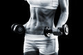 Body of a young fit woman lifting dumbbells on dark background Stock Photos