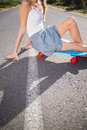 Body of young woman sitting on her skateboard a deserted road Royalty Free Stock Photography