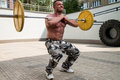 Bodybuilder doing front squats with barbells barbell outdoors Royalty Free Stock Image