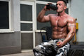 Bodybuilder drinking man holding and the post workout chocolate whey protein shake Stock Image