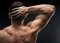 Bodybuilder hand in the dark threw a strong arm behind your head Stock Photos