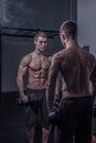 Bodybuilder, looking at himself, holding dumbbells Royalty Free Stock Photo