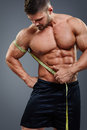 Bodybuilder measuring biceps with tape measure Royalty Free Stock Photo