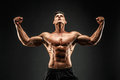 Bodybuilder posing. Fitness muscled man on dark background. Royalty Free Stock Photo
