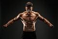 Bodybuilder posing. Fitness muscled man on dark background. Roaring for motivation. Royalty Free Stock Photo