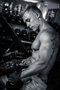 Bodybuilder sitting with weights in the gym standing a dumbbell after training monochrome Stock Image