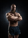 Bodybuilder topless over grunge background. Royalty Free Stock Photo