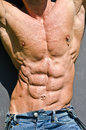 Bodybuilder torso with arms up ripped abs and pecs with nipple piercing wearing jeans Royalty Free Stock Photography