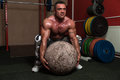 Bodybuilder trying a strongman exercise muscular man to pick up stone workout Stock Image