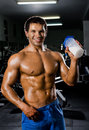 Bodybuilder the very muscular sporty guy drinking protein in dark weight room naked torso Royalty Free Stock Image