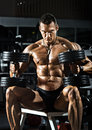 Bodybuilder very power athletic guy sit with dumbbells in dark gym Stock Photos
