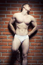 Bodybuilder young athlete man near brick wall Royalty Free Stock Photos