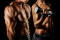 Bodybuilding man and woman strong a posing on a black background Stock Photos