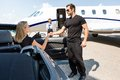 Bodyguard helping elegant woman stepping out of women car at airport terminal Stock Image