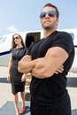 Bodyguard standing against woman and private jet with arms crossed women Stock Image