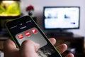 Boekarest roemenië november foto van hand die een iphone met nieuws apps op het scherm en tv reeks op de achtergrond houden met Stock Afbeeldingen