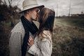 Boho gypsy woman and man in hat kissing in windy field. stylish Royalty Free Stock Photo