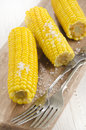 Boiled corn cobs with coarse salt on a wooden board Royalty Free Stock Photography