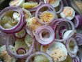 Organic sliced red onions in a potato salad Royalty Free Stock Photo