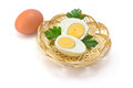 Boiled eggs one egg two halves of and parsley leaves in a straw plate Royalty Free Stock Photo