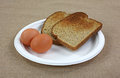 Boiled eggs toast on plate two with wheat Royalty Free Stock Photography