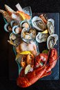Boiled lobster, fresh oysters, shrimps, mussels and clams served in black stone plate
