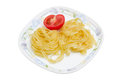 Boiled noodles and half fresh tomato on dish Royalty Free Stock Photo