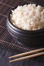Boiled rice in a black bowl close-up and chopsticks. vertical Royalty Free Stock Photo