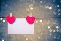 与垂悬在蓝色和金  的bokeh背景,情人节的概念的 卡的两装饰红色心脏 免版税库存图片
