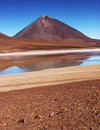 Bolivia volcano in bolivian altiplano with lagoon in foreground Royalty Free Stock Photo