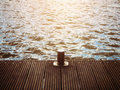 Bollard on wood wooden pier against sunlight over water Stock Photos