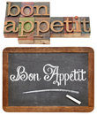 Bon appetit typography white chalk text on a vintage slate blackboard and isolated text in letterpress wood type Royalty Free Stock Images