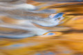 Bond falls rapids cascade captured with motion blur and illuminated by reflected color from sunlit autumn maples and blue sky Royalty Free Stock Photos