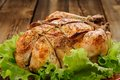 Bondage shibari roasted chicken with salad leaves on red plate o wooden background closeup horizontal Royalty Free Stock Images